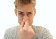 мужчина закрывает нос