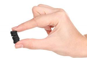 черные таблетки в руке